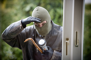 a burglar breaking in the window of a house