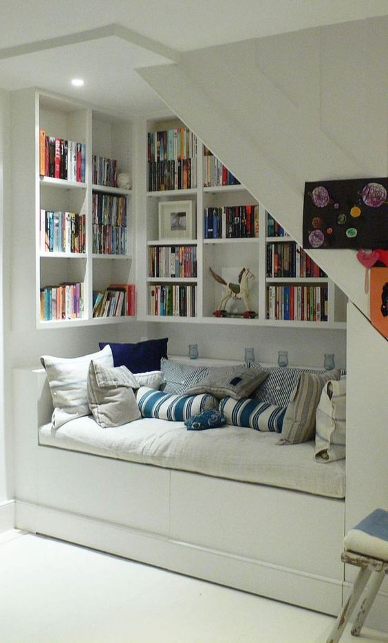 library under stairs with sofa
